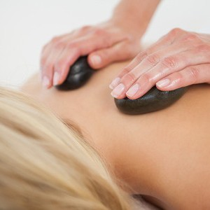 A female receiving a hot stone massage